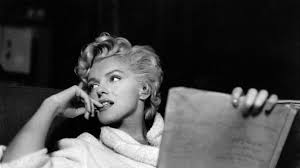 Marilyn Monroe reading a script in a white bathrobe.